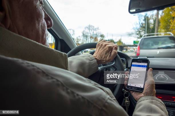 Irresponsible elderly man at steering wheel checking messages on smart phone smartphone cellphone while driving car on road