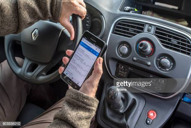 Irresponsible man at steering wheel checking messages on smart phone smartphone cellphone while driving car on road