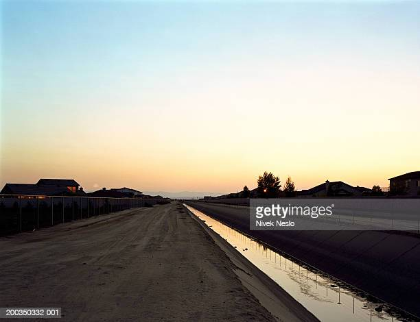 Irrigation canal and houses, sunset