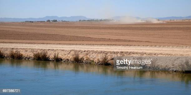 irrigation canal; tractors preparing field beyond - timothy hearsum stock-fotos und bilder