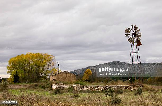 Irrigation pond with a metal windmill in autumn
