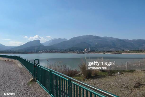 irrigation pond with a mosque on the other side in kemalpasa. - emreturanphoto stock pictures, royalty-free photos & images