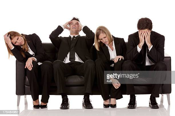 Irritated business executives sitting on a couch