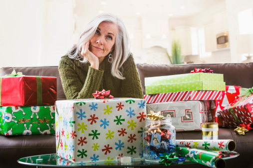 Irritated Caucasian woman wrapping Christmas gifts - gettyimageskorea