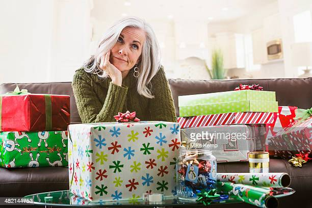 Irritated Caucasian woman wrapping Christmas gifts