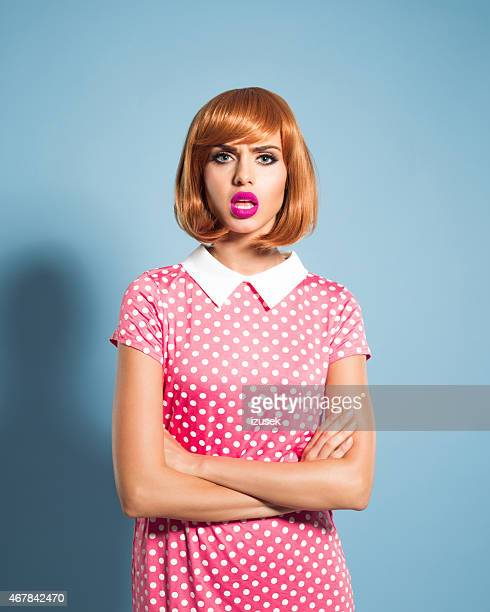 Irritated red hair young woman wearing polka dot dress