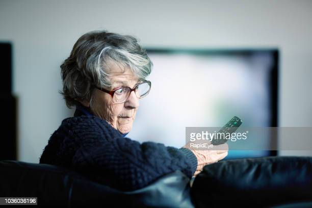 irritated senior woman battles to use tv remote - television show stock pictures, royalty-free photos & images