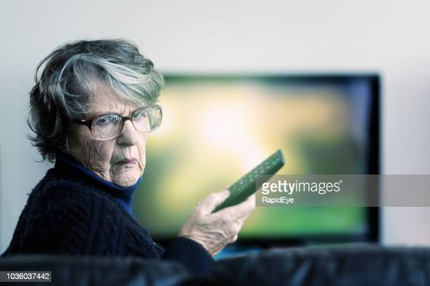 irritated senior woman battles with tv remote looks round angrily - cross stock pictures, royalty-free photos & images