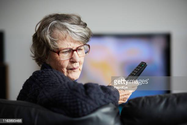 irritated senior woman cannot work tv remote control - ineptitude stock pictures, royalty-free photos & images