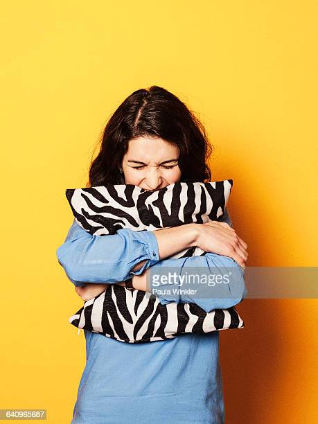 irritated young woman embracing cushion against yellow background - cushion stock photos and pictures