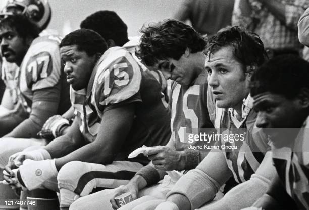 Irv Pankey Vince Ferragamo and Dennis Harrah of the Los Angeles Rams sit on the bench during a game at Anaheim Stadium Anaheim California