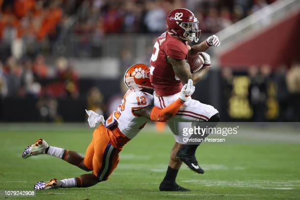 Irv Smith Jr #82 of the Alabama Crimson Tide is tackled by K'Von Wallace of the Clemson Tigers during the first quarter in the CFP National...