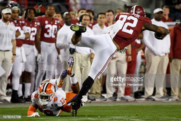 Irv Smith Jr #82 of the Alabama Crimson Tide leaps over K'Von Wallace of the Clemson Tigers during the first quarter in the CFP National Championship...
