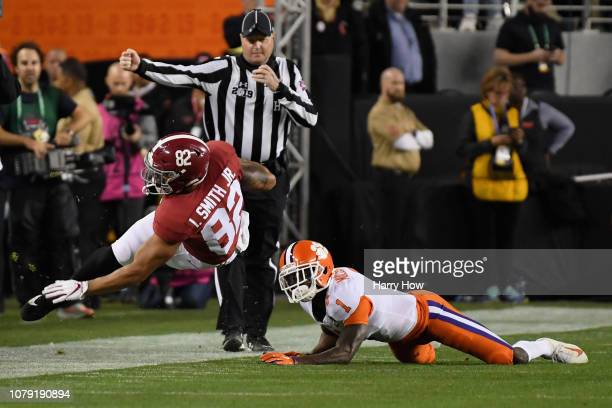 Irv Smith Jr #82 of the Alabama Crimson Tide leaps past Trayvon Mullen of the Clemson Tigers during the first quarter in the CFP National...