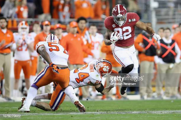 Irv Smith Jr #82 of the Alabama Crimson Tide looks to get past Nolan Turner of the Clemson Tigers during the second half in the CFP National...