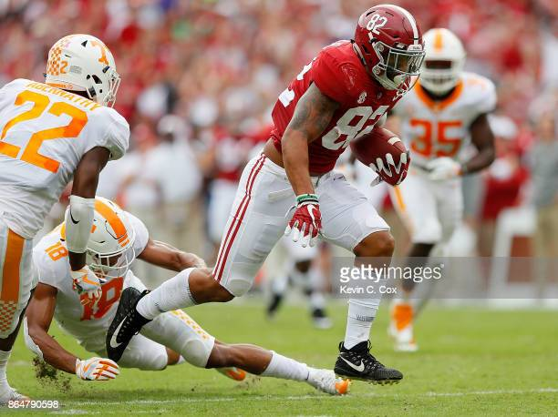 Irv Smith Jr #82 of the Alabama Crimson Tide rushes away from Nigel Warrior and Micah Abernathy of the Tennessee Volunteers at BryantDenny Stadium on...