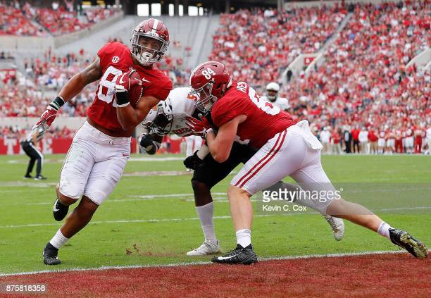 Irv Smith Jr #82 of the Alabama Crimson Tide scores a touchdown against Malique Fleming of the Mercer Bears at BryantDenny Stadium on November 18...