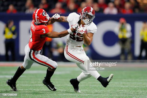 Irv Smith Jr #82 of the Alabama Crimson Tide stiff arms Tyson Campbell of the Georgia Bulldogs in the first half during the 2018 SEC Championship...