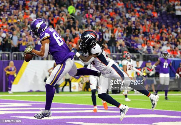 Irv Smith Jr #84 of the Minnesota Vikings makes his first career NFL touchdown pass reception against Davontae Harris of the Denver Broncos in the...