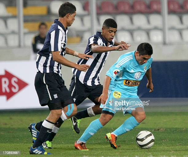 Irvin Avila of Sporting Cristal fights for the ball with Wilder Cartagena and Koichi Aparicio of Alianza Lima during a match between Sporting Cristal...