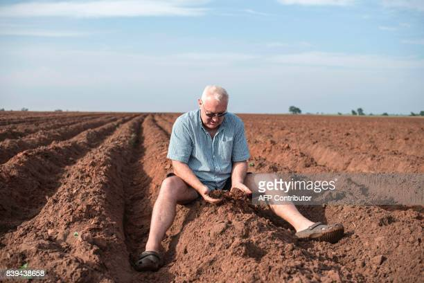 Irvine Reid manager of Rosedale Dairy Farm inspects the soil of a recently prepared land for cassava production on July 12 2017 Farming in Nigeria is...