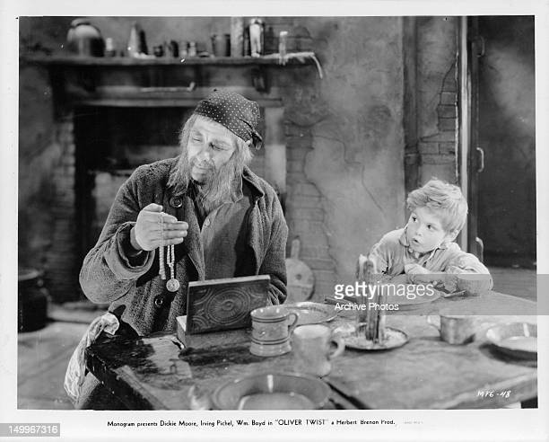 Irving Pichel holding jewelry in front of an amazed Dickie Moore in a scene from the film 'Oliver Twist', 1933.