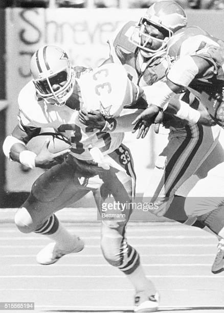 Irving, Tex.: The Dallas Cowboys' Tony Dorsett runs through the grasp of Philadelphia Eagles' Brenard Wilson and Ray Ellis during a first half short...