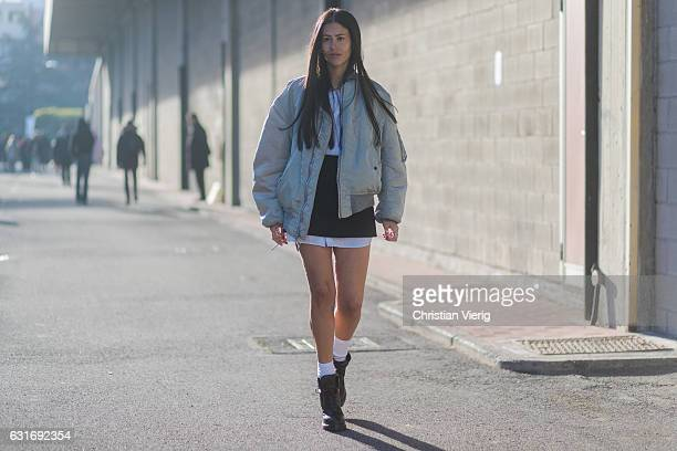 is Gilda Ambrosio is wearing bomber jacket an off shoulder dress with sleeves socks ankle boots mini skirt seen at Diesel during Milan Men's Fashion...