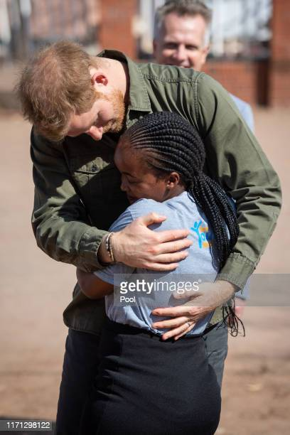 is greeted by Tlotlo Moilwa during a visit to the Kasane Health Post run by the Sentebale charity in Kasane on day four of their tour of Africa on...