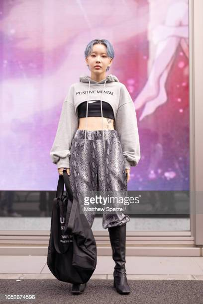 HYOXXI is seen wearing grey crop hoodie grey snakeskin pattern pants black boots and tote bag during the Amazon Fashion Week TOKYO 2019 S/S on...