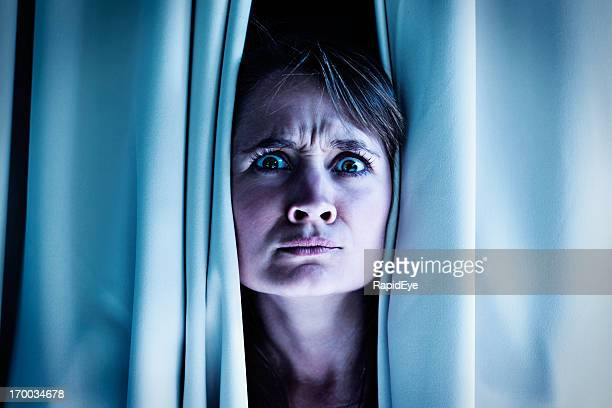 Is that an intruder? Nervous blonde frowns through curtains