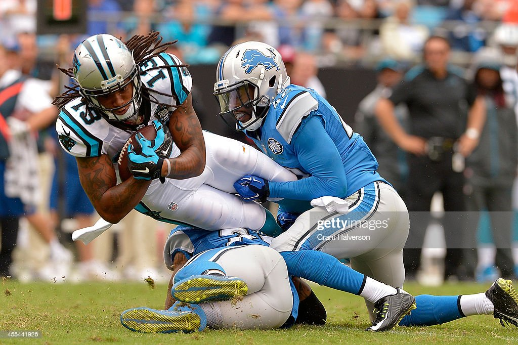 Isa Abdul-Quddus #42 of the Detroit Lions tackles Kelvin Benjamin #13 of the Carolina Panthers during their game at Bank of America Stadium on September 14, 2014 in Charlotte, North Carolina.