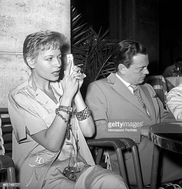 Isa Barzizza looks into the lens of a Minox AIII ready to take a photograph the famous revue actress is seated at the outdoor table of a bar beside...