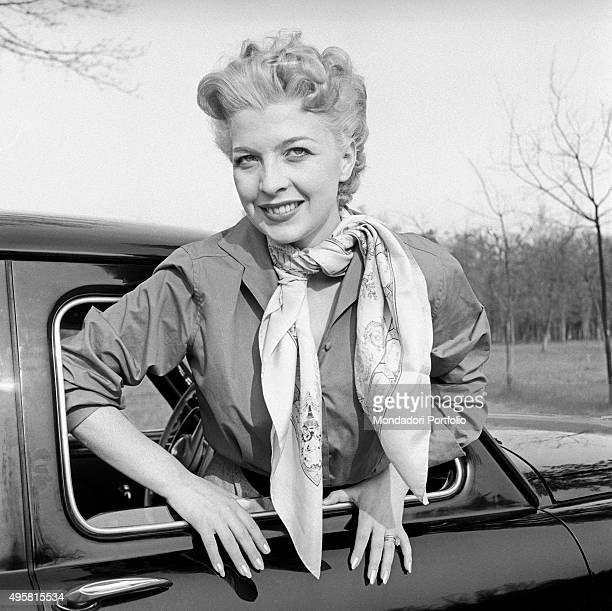 Isa Barzizza wearing a stylish foulard around her neck sticks out the window of a car the multifaceted actress ironic and exceptionally gifted with...