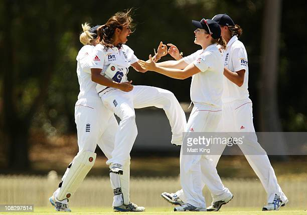 Isa Guha of England is lifted by team mates after taking the wicket of Shelley Nitschke of Australia during day four of the Women's CBA Test match...