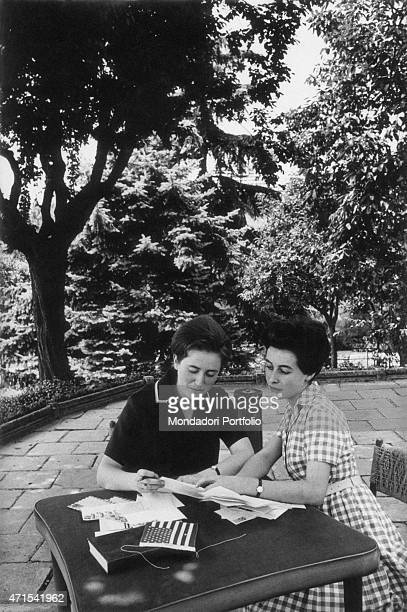 Isa Signorini on the left and Lina Manera two students of the Istituto Tecnico Commerciale of Alba sitting at a table in a patio in the middle of a...