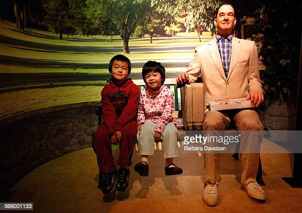 Isaac and Olivia Yang sit next to wax figure of Forrest Gump as their parents take pictures Dec 20 2011 at the Hollywood Wax Museum Madame Tussauds...