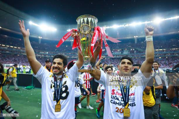 Isaac Brizuela and Alan Pulido of Chivas celebrate with the champion trophy during the second leg match of the final between Chivas and Toronto FC as...