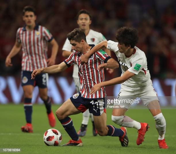 Isaac Brizuela of CD Guadalajara battles for possession with Shuto Yamamoto of Kashima Antlers during the FIFA Club World Cup UAE 2018 Second round...