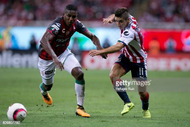 Isaac Brizuela of Chivas fights for the ball with Brayan Beckeles of Necaxa during the third round match between Chivas and Necaxa as part of the...