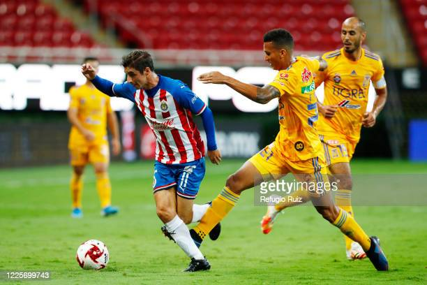 Isaac Brizuela of Chivas fights for the ball with Francisco Meza of Tigres during the match between Chivas and Tigres UANL as part of the friendly...