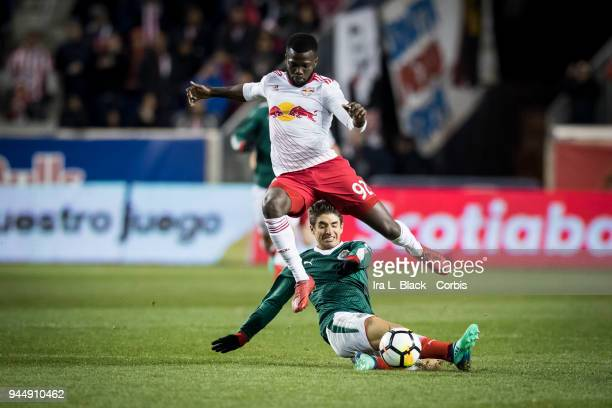 Isaac Brizuela of Guadalajara slides in to steal the ball from Kemar Lawrence of New York Red Bulls during the CONCACAF Champions League Semifinals...