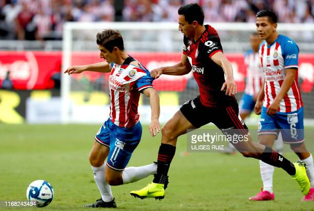 Isaac Brizuela of Guadalajara vies for the ball with Ismael Govea of Atlas during their Mexican Apertura 2019 tournament football match at the Akron...