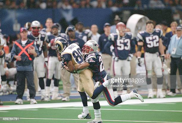 Isaac Bruce of St. Louis Rams catches a pass and gets tackled by Ty Law of the New England Patriots during Super Bowl XXXVI at the Louisiana...
