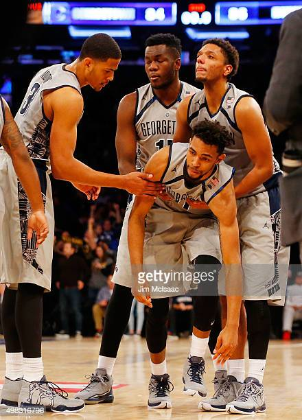 Isaac Copeland of the Georgetown Hoyas is helped up by his teammates after missing a potential game tying shot at the buzzer against the Duke Blue...