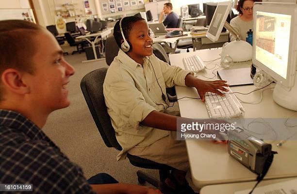 DENVER CO JUN 19 2003 Isaac <cq> Anthony <cq> 16 <cq> of Denver North High school <cq> left helps Jasser <cq> Mohamed <cq> 13 <cq> of Hamilton Middle...