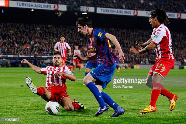 Isaac Cuenca of FC Barcelona duels for the ball with Alberto Botia of Sporting de Gijon and Andre Castro of Sporting de Gijon during the La Liga...