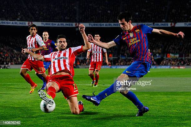 Isaac Cuenca of FC Barcelona shoots towards goal under a challenge by Alberto Botia of Sporting de Gijon during the La Liga match between FC...