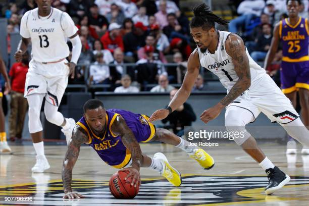 Isaac Fleming of the East Carolina Pirates dives for a loose ball ahead of Jacob Evans of the Cincinnati Bearcats in the second half of a game at...