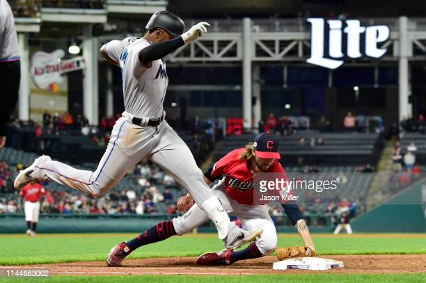 Isaac Galloway of the Miami Marlins is forced out at first base by pitcher Adam Cimber of the Cleveland Indians during the ninth inning at...